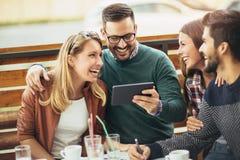Ομάδα τεσσάρων φίλων που έχουν τη διασκέδαση ένας καφές από κοινού Στοκ Εικόνες