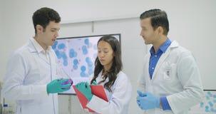 Ομάδα της συζήτησης επιστημόνων ιατρικής έρευνας τα συμπεράσματά τους στο εργαστήριο φιλμ μικρού μήκους