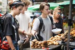 Ομάδα τουριστών που αγοράζουν τα ταϊλανδικά τρόφιμα στο στάβλο τροφίμων Στοκ Φωτογραφία