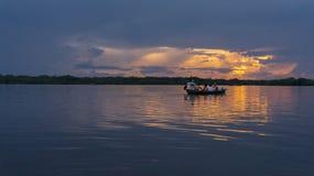 Ομάδα τουριστών στη βάρκα που πλέει στη λιμνοθάλασσα Cuyabeno στο ηλιοβασίλεμα στοκ φωτογραφία