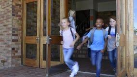Ομάδα του δημοτικού σχολείου παιδιών που τρέχουν έξω από το σχολείο απόθεμα βίντεο