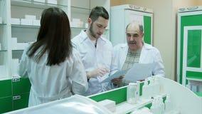 Ομάδα του φαρμακοποιού που ελέγχει τα έγγραφα και την ιατρική στο φαρμακείο απόθεμα βίντεο