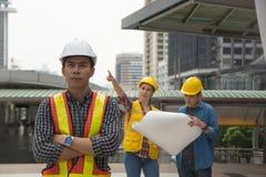 Ομάδα των αρχιτεκτονικών που στέκονται στο εργοτάξιο οικοδομής που εξετάζει το π στοκ φωτογραφίες