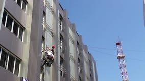 Ομάδα των βιομηχανικών ορειβατών στην εργασία, πλένουν την πρόσοψη οικοδόμησης φιλμ μικρού μήκους