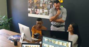 Ομάδα των γραφικών σχεδιαστών που συζητούν πέρα από τον υπολογιστή στο γραφείο 4k απόθεμα βίντεο