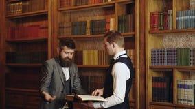 Ομάδα των δικηγόρων στη βιβλιοθήκη νόμου στο πανεπιστήμιο Δικηγόροι που διαβάζουν το βιβλίο και που συζητούν στη βιβλιοθήκη νόμου απόθεμα βίντεο