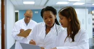 Ομάδα των επιστημόνων που συζητούν πέρα από ένα lap-top 4k φιλμ μικρού μήκους