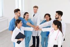 Ομάδα των ιατρικών εργαζομένων που κρατούν τα χέρια μαζί στο νοσοκομείο στοκ εικόνες