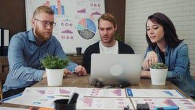 Ομάδα των νέων Διευθυντών επιχείρησης που αναλύουν τα στοιχεία που χρησιμοποιούν τον υπολογιστή στο γραφείο φιλμ μικρού μήκους
