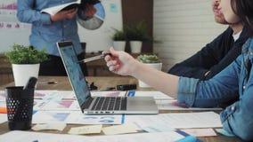 Ομάδα των νέων Διευθυντών επιχείρησης που αναλύουν τα στοιχεία που χρησιμοποιούν τον υπολογιστή στο γραφείο απόθεμα βίντεο