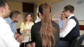Ομάδα των νέων επιχειρηματιών που εργάζονται μαζί στη συνεδρίαση γραφείων στο γραφείο γραφείων και που συζητούν το νέο πρόγραμμα απόθεμα βίντεο