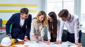 Ομάδα των νέων επιχειρηματιών που συζητούν το blueprin στοκ φωτογραφία
