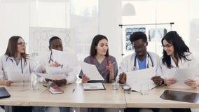 Ομάδα των multiethnic νέων γιατρών που διοργανώνουν μια συνεδρίαση στη αίθουσα συνδιαλέξεων στο σύγχρονο νοσοκομείο Ομάδα multiet φιλμ μικρού μήκους