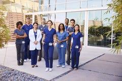 Ομάδα υγειονομικής περίθαλψης με τη στάση διακριτικών ταυτότητας υπαίθρια, πλήρες μήκος στοκ φωτογραφίες