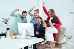 Ομάδα υπαλλήλων γραφείων που γιορτάζουν τη νίκη στοκ εικόνα