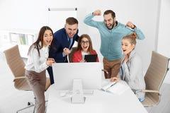 Ομάδα υπαλλήλων γραφείων που γιορτάζουν τη νίκη στοκ φωτογραφία