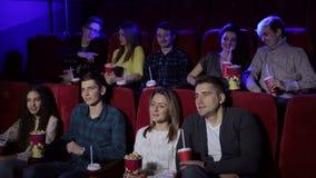 Ομάδα φίλων εφήβων στον κινηματογράφο που προσέχει έναν κινηματογράφο και που τρώει popcorn απόθεμα βίντεο