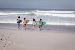 Ομάδα φίλων με την ιστιοσανίδα που τρέχει προς τη θάλασσα στην παραλία στην ηλιοφάνεια στοκ φωτογραφία με δικαίωμα ελεύθερης χρήσης