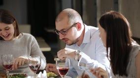 Ομάδα φίλων που έχουν το μεσημεριανό γεύμα στο εστιατόριο Άνδρας και δύο γυναίκες που έχουν το μεσημεριανό γεύμα στο εστιατόριο κ φιλμ μικρού μήκους