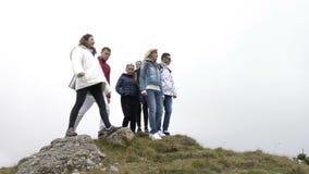 Ομάδα φίλων που αναρριχούνται επάνω και που φθάνουν στην κορυφή βουνών που πηδά και που αυξάνει τα όπλα που απολαμβάνουν την επιτ απόθεμα βίντεο