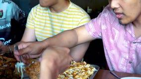 Ομάδα φίλων που απολαμβάνουν τρώγοντας τα δυτικά τρόφιμα σε έναν δίσκο μετάλλων από Burger A&J τη σχάρα απόθεμα βίντεο