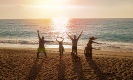 Ομάδα φίλων που διαμορφώνει τις επιστολές αγάπης στην παραλία στο ηλιοβασίλεμα στοκ εικόνα