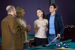 Ομάδα φίλων που παίζουν το μπιλιάρδο και που χαμογελούν στο δωμάτιο μπιλιάρδου Στοκ Φωτογραφίες