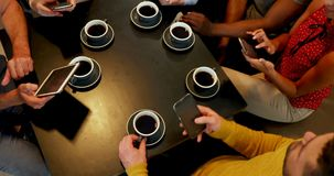 Ομάδα φίλων που χρησιμοποιούν κινητή ενώ έχοντας τον καφέ 4K 4k απόθεμα βίντεο
