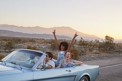 Ομάδα φίλων στο οδικό ταξίδι που το κλασικό μετατρέψιμο αυτοκίνητο στοκ εικόνες