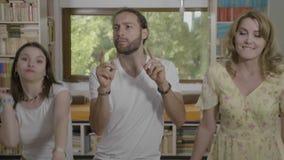 Ομάδα χαλαρωμένων ευτυχών φίλων που απολαμβάνουν τη μουσική ακούσματος και χορός μαζί στο σπίτι κόμμα - απόθεμα βίντεο