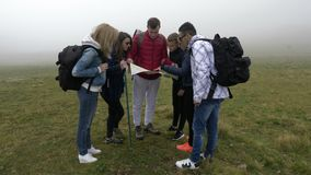 Ομάδα χαμένων νέων τουριστών που ψάχνοντας την ομίχλη γουρνών κατεύθυνσης που διαβάζει το χάρτη σε μια κορυφή βουνών - απόθεμα βίντεο