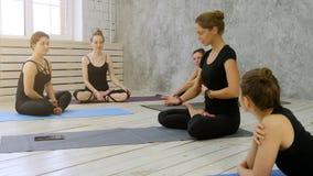 Ομάδα χαμογελώντας γυναικών talkin με τον εκπαιδευτικό γιόγκας μετά από να εκπαιδεύσει στο στούντιο ικανότητας Στοκ Εικόνα