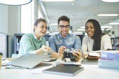 Ομάδα χαμογελώντας σπουδαστών που έχουν τη διασκέδαση στην πανεπιστημιακή βιβλιοθήκη Στοκ Εικόνα