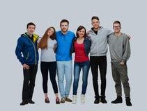 Ομάδα χαμογελώντας φίλων που μένουν μαζί και που εξετάζουν τη κάμερα που απομονώνεται στο άσπρο υπόβαθρο Στοκ Εικόνες