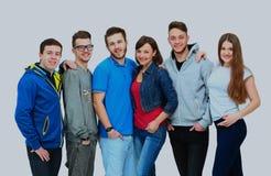 Ομάδα χαμογελώντας φίλων που μένουν μαζί και που εξετάζουν τη κάμερα που απομονώνεται στο άσπρο υπόβαθρο Στοκ φωτογραφία με δικαίωμα ελεύθερης χρήσης