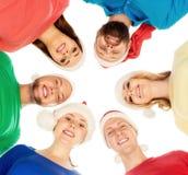 Ομάδα χαμογελώντας φίλων στα καπέλα Χριστουγέννων που αγκαλιάζει από κοινού Στοκ εικόνα με δικαίωμα ελεύθερης χρήσης