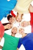 Ομάδα χαμογελώντας φίλων στα καπέλα Χριστουγέννων που αγκαλιάζει από κοινού Στοκ Εικόνες