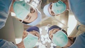 Ομάδα χειρούργων που έχουν μια συνομιλία πέρα από το λειτουργούντα πίνακα απόθεμα βίντεο