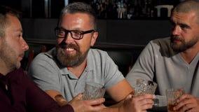 Ομάδα ώριμων αρσενικών φίλων που γελούν και που μιλούν πέρα από το ποτήρι του ουίσκυ στο φραγμό απόθεμα βίντεο