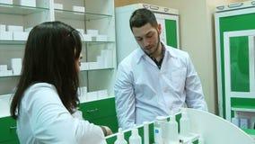 Ομάδα Dissapointed των αποθηκαρίων στο φαρμακείο που στέκεται μπροστά από την ομιλία ραφιών απόθεμα βίντεο