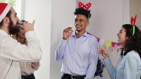 Ομάδα Multiethnic νέων εργαζομένων γραφείων που τα γυαλιά με το λαμπιρίζοντας κρασί που φορά τα καπέλα και τον εορτασμό Χριστουγέ φιλμ μικρού μήκους