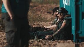 Ομάδα rocker ατόμων που κάθονται στο έδαφος που κλίνει στο εμπορευματοκιβώτιο φορτίου απόθεμα βίντεο