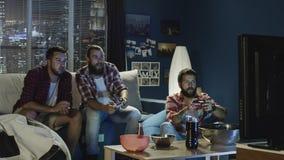 Ομάδα videogame παιχνιδιού ατόμων μαζί το βράδυ Στοκ Φωτογραφίες