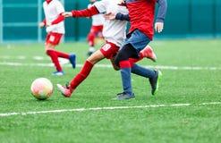 Ομάδες ποδοσφαίρου - αγόρια στο κόκκινο, μπλε, άσπρο ομοιόμορφο ποδόσφαιρο παιχνιδιού στον πράσινο τομέα ροή αγοριών δεξιότητες ρ στοκ φωτογραφίες με δικαίωμα ελεύθερης χρήσης
