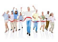 Ομάδα ανθρώπων που διασχίζει τη γραμμή τερματισμού στοκ εικόνες