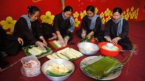 Ομάδα ανθρώπων που κατασκευάζει τα παραδοσιακά τρόφιμα του Βιετνάμ για το σεληνιακό νέο YE Στοκ Εικόνα