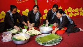 Ομάδα ανθρώπων που κατασκευάζει τα παραδοσιακά τρόφιμα του Βιετνάμ για Tet Στοκ Εικόνα