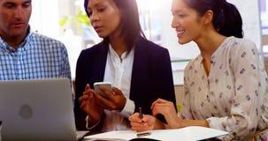 Ομάδα ανώτατων στελεχών επιχείρησης που συζητούν πέρα από το lap-top στο γραφείο τους φιλμ μικρού μήκους