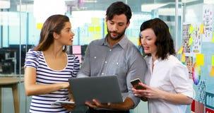 Ομάδα ανώτερων υπαλλήλων που συζητούν πέρα από το lap-top φιλμ μικρού μήκους