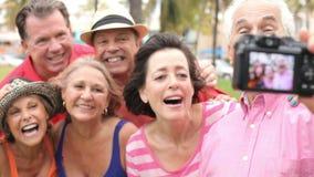 Ομάδα ανώτερων φίλων που παίρνουν Selfie στο πάρκο απόθεμα βίντεο